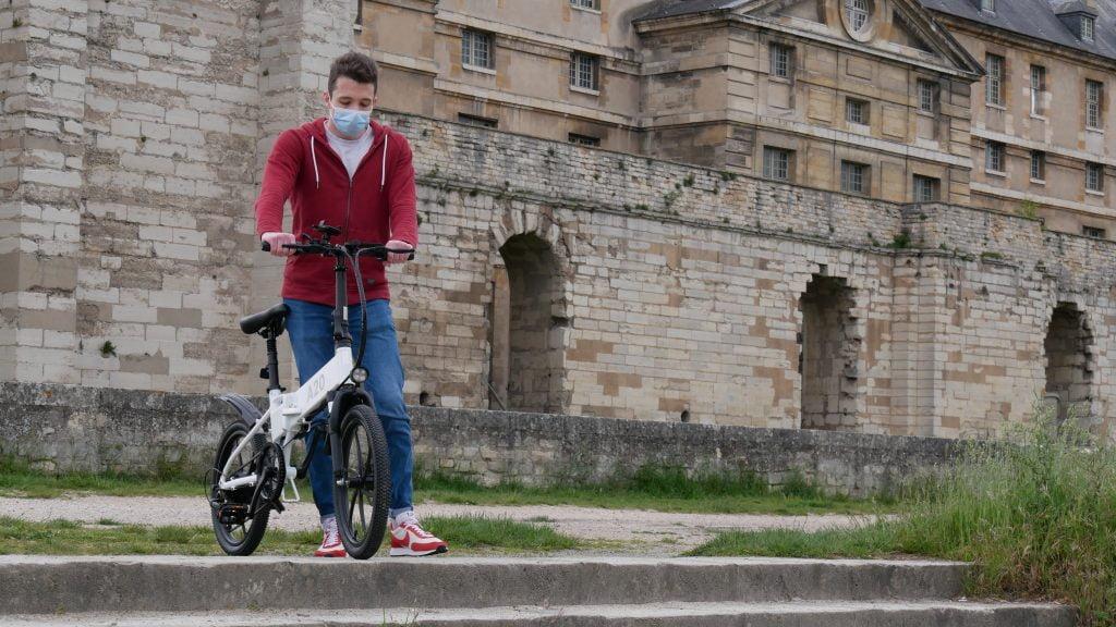 Vélo électrique Ado-A20 en haut d'un escalier avec son utilisateur debout les mains sur le guidon