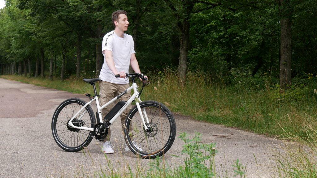 photo du vélo électrique radmission 1  de profil avec son utilisateur les mains sur le guidon et les deux pieds à terre