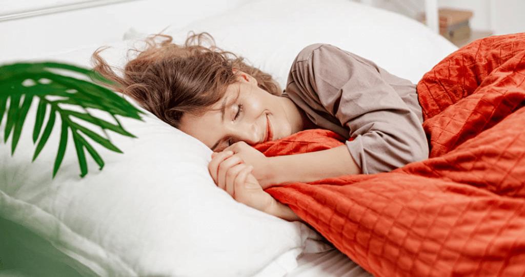 une femme qui dort avec une couverture gravité rouge